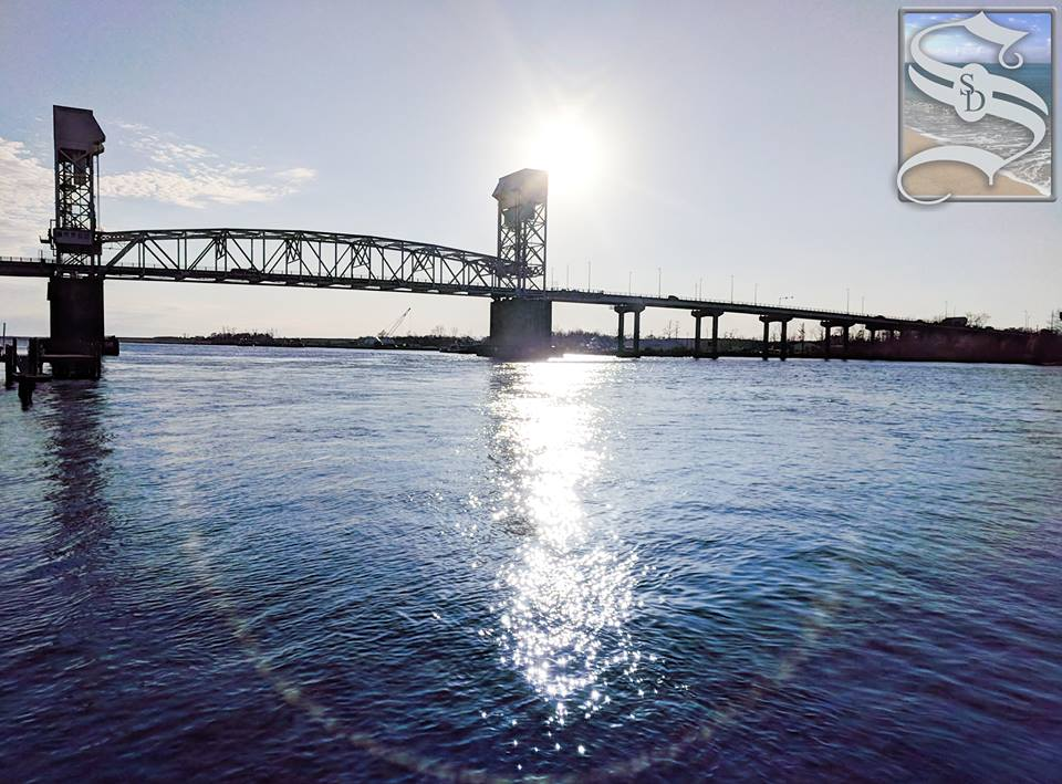 Cape Fear Bridge with sun behind it