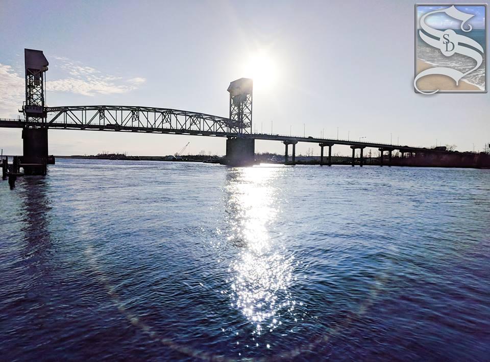 Cape Fear Bridge with sun behind it